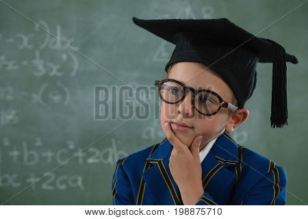 Thoughtful schoolboy in mortar board standing against chalkboard