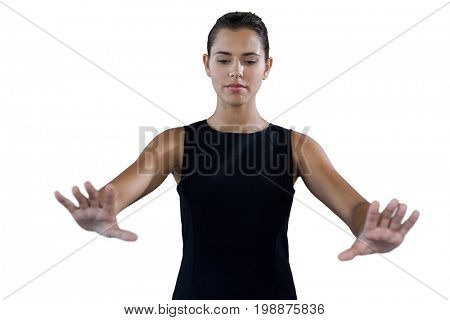 Businesswoman using invisible interface while standing against white background