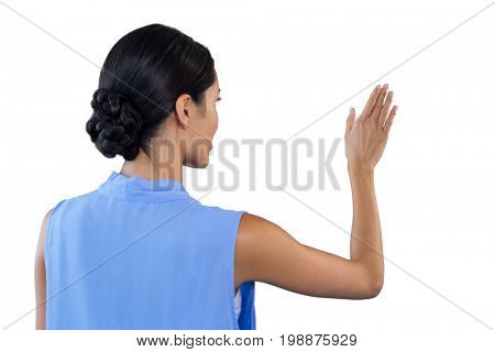 Rear view of businesswoman touching interface against white background