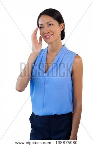 Smiling thoughtful businesswoman looking away while gesturing against white background