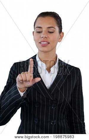 Businesswoman in suit touching invisible interface while standing against white background