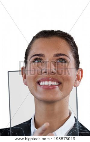 Close up of smiling businesswoman looking up while using glass interface against white background