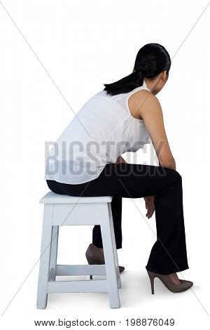 Full length of woman sitting on stool against white background