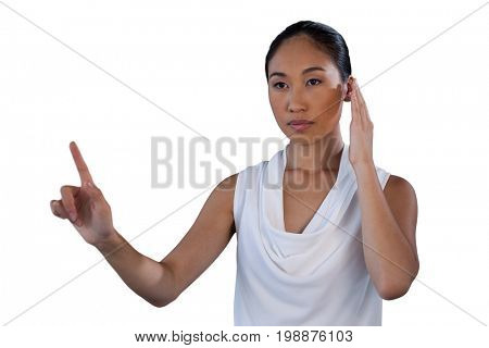 Serous businesswoman pretending to answer call while touching invisible interface against white background