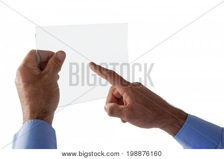 Cropped hand on businessman using glass interface against white background