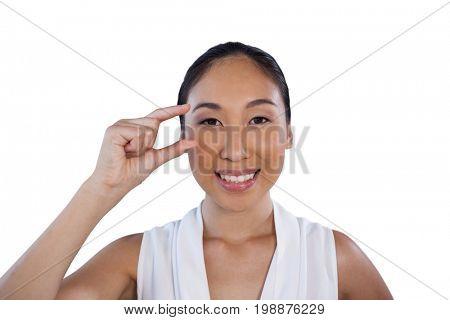 Portrait of happye businesswoman adjusting invisible eyeglasses against white background