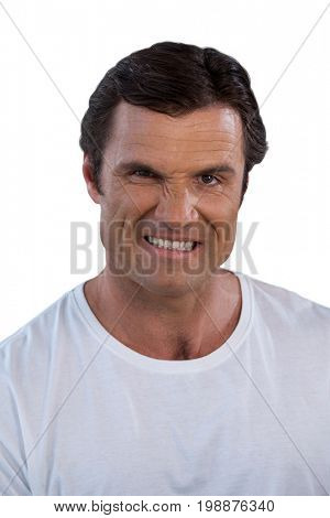 Portrait of mature man clenching teeth against white background