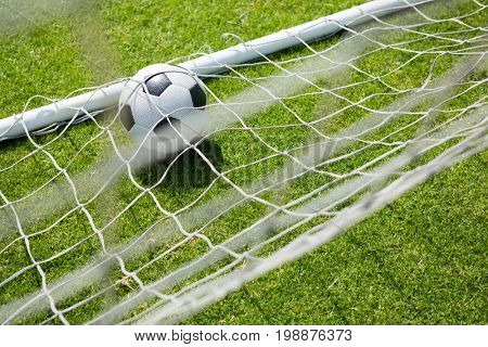 High angle view of soccer ball in goal post at field