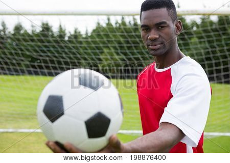 Portrait of male soccer player holding ball while standing against goal post