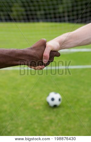 Close up of soccer player doing handshake while standing on playing field