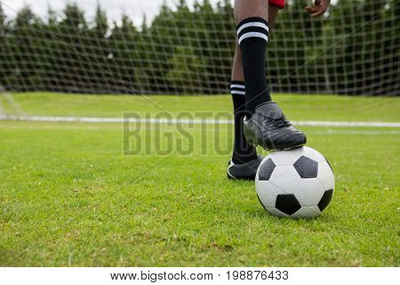 Low section of male soccer player with ball on field by goal post