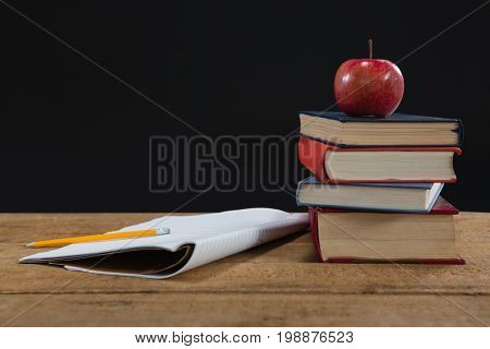 Book stack, pencil and apple on wooden table against black background