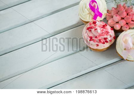 High angle view of Breast Cancer Awareness pink ribbons on cupcakes over white wooden table
