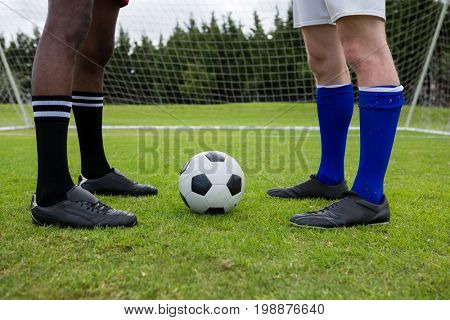 Low section of male soccer players with ball on field against goal post