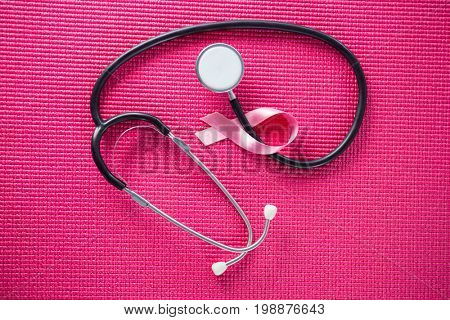Overhead view of stethoscope by pink Breast Cancer Awareness ribbon on fabric