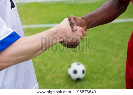 Cropped image of soccer player doing handshake while standing on playing field