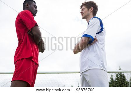 Low angle view of young male soccer players looking at each other while standing against sky