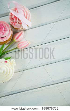 Overhead view of Breast Cancer Awareness pink ribbons on cupcakes with tulips over white wooden table