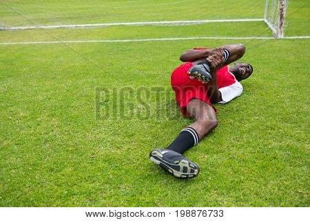 Young male soccer player suffering from knee pain lying down on playing field