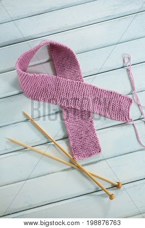 High angle view of pink woolen Breast Cancer Awareness ribbon by crochet needles on white wooden table