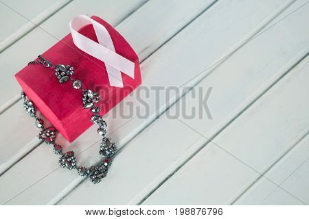 High angle view of jewelry with red box and pink Breast Cancer Awareness ribbon on wooden table