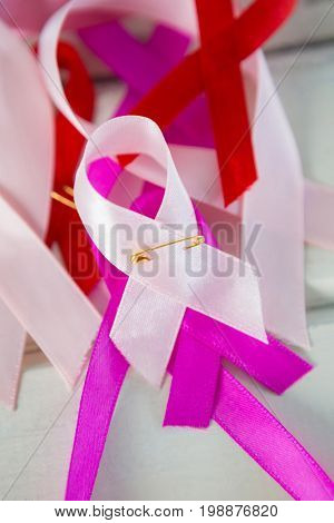 High angle view of various Cancer Awareness ribbons on white wooden table