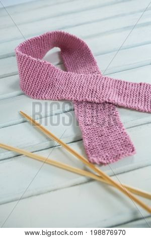 Close-up of pink woolen Breast Cancer Awareness ribbon by crochet needles on white wooden table