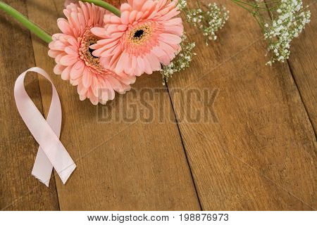 Close-up of pink Breast Cancer Awareness ribbon by gerbera flowers on wooden table