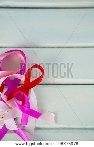 Directly above view of Cancer Awareness ribbons on white wooden table