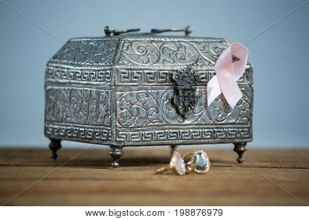 Surface level view of pink Breast Cancer Awareness ribbon with chest and rings on wooden table against white background