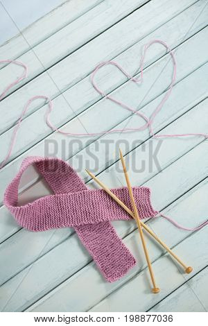 High angle view of pink Breast Cancer Awareness ribbon by crochet needles with heart shape on white wooden table