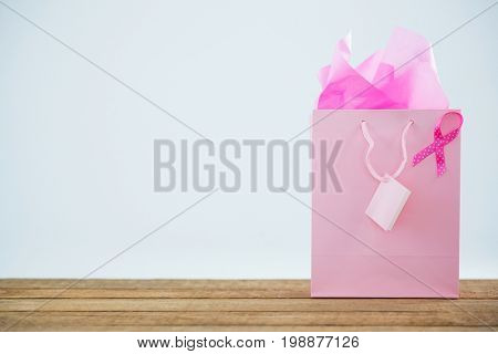 Pink Breast Cancer Awareness ribbon on shopping bag over wooden table against white background