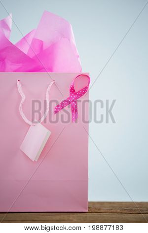 Close-up of pink spotted Breast Cancer Awareness ribbon on shopping bag against white background