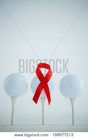 Red AIDS Awareness ribbon on golf ball against white background