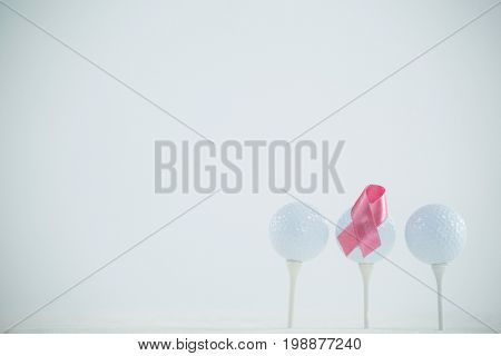Pink Breast Cancer Awareness ribbon on golf ball against white background