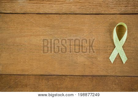 Directly above view of spotted green Lymphoma Awareness ribbon on wooden table