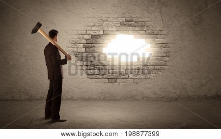 Business man hitting brick grungy wall with hammer and opening a hole
