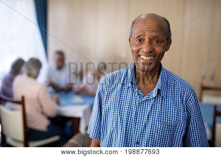 Portrait of smiling senior man standing against friends at nursing home