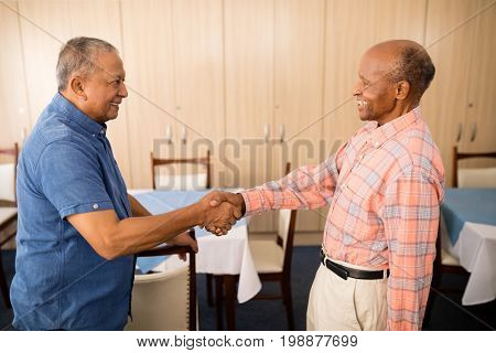 Smiling senior man doing handshake with friend while standing at nursing home