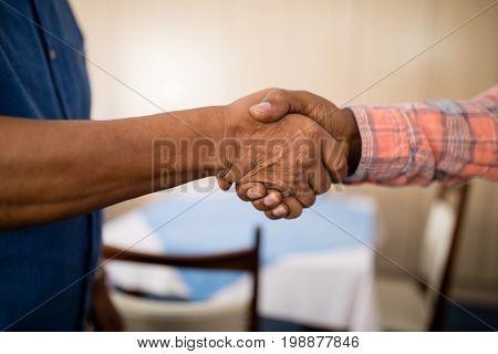 Cropped image of senior friends doing handshake at nursing home