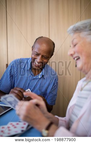 Smiling senior man and woman playing cards at table in nursing home