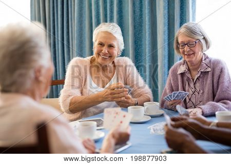 Smiling senior female friends playing cards while having coffee at table in nursing home