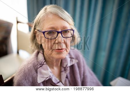 Portrait of senior woman wearing eyeglasses sitting on chair at nursing home