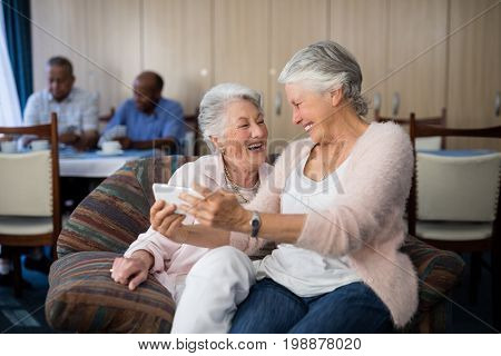 Happy senior woman taking selfie through mobile phone while sitting on sofa at nursing home