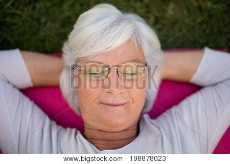 High angle view of senior woman resting with closed eyes on exercise mat at park