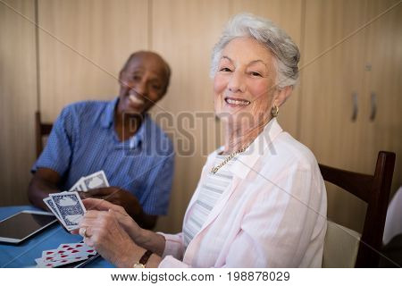 Portrait of senior woman playing cards with friend while sitting at table in nursing home
