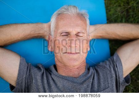 High angle view of senior man resting with closed eyes on exercise mat at park