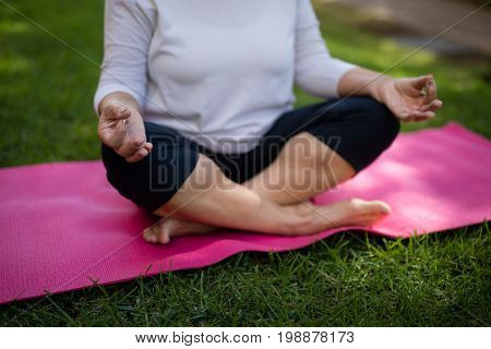 Mid section of senior woman meditating while sitting on exercise mat at park