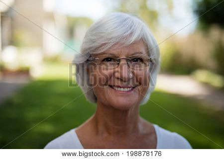 Close-up of smiling senior woman wearing eyeglasses at park