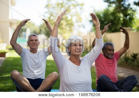 Senior people exercising with hands raised while sitting at park